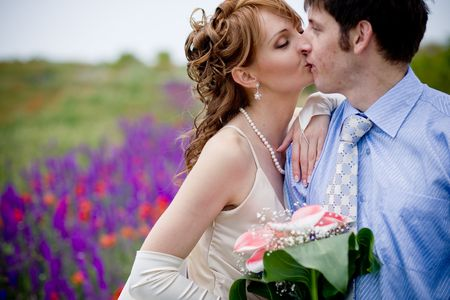 Bride and groom kissing in field of flowers photo