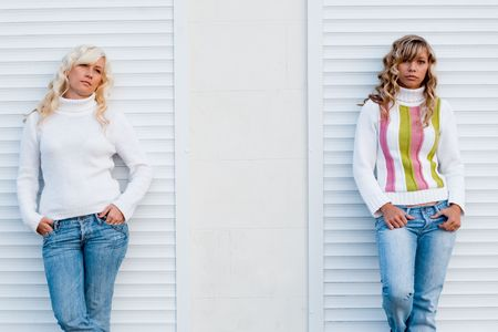 jalousie: Two young adult sisters wearing sweaters and jeans posing over white jalousie Stock Photo