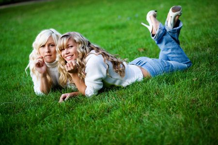 Two girls lying together in fresh grass outdoors. photo
