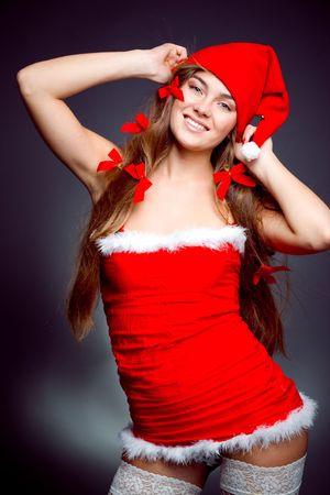 Sexy santa helper girl with long beautiful hair wearing stocking posing on gray studio background photo