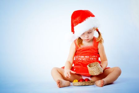 Cute Santa child playing with Christmas decorations on blue studio background