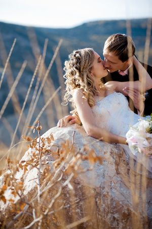 Kissing wedding couple on a stone outdoors Stock Photo