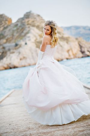 woman beach dress: Beautiful bride wearing fluffy wedding dress posing at beach