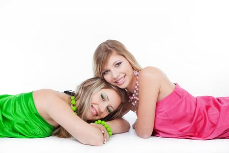 Two beautiful blond models posing over white photo