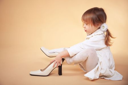 infant girl: Funny little girl trying adult shoes