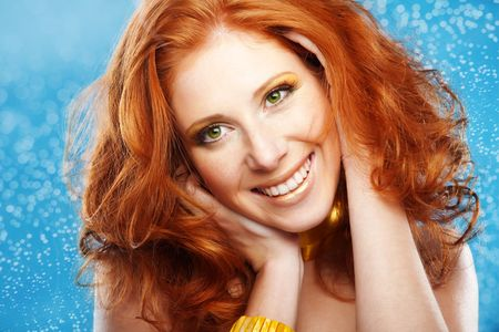 Portrait of beautiful redheaded girl on bue textured background photo