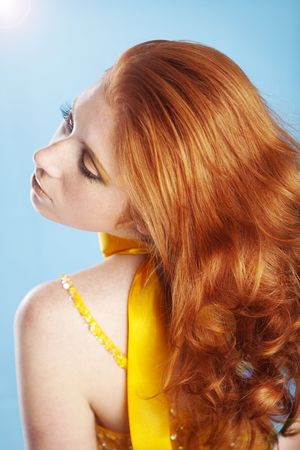 Posing woman with beautiful red hair on blue background photo