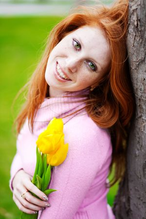 Portrait of beautiful smiling girl with spring flowers posing in park photo