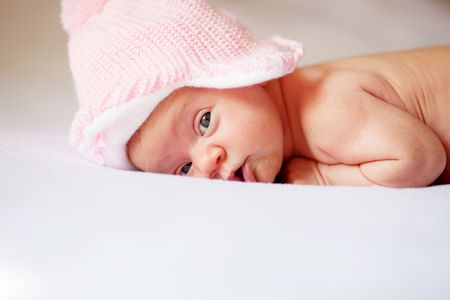 Sweet newborn wearing pink knitted hat lying on white Stock Photo - 4523819