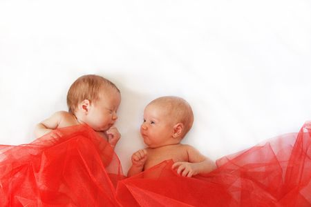Lovely twins on white covered with red textile Stock Photo