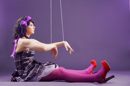 Fashion model stylized as marionette doll sitting on violet studio background photo