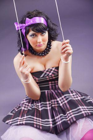 Fashion model stylized as marionette doll sitting on violet studio background Stock Photo