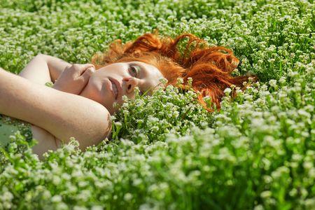 Young beautiful girl lying in fresh grass photo