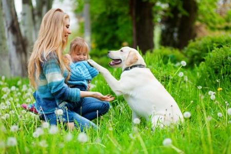 perro labrador: Bella mujer con ni�a y perro al aire libre