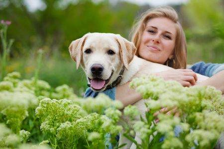 spring training: Girl with her dog posing in spring grass