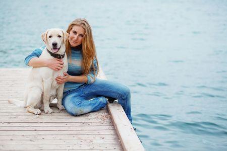 trusting: Beautiful girl with her dog on berth near sea Stock Photo
