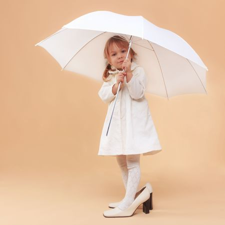 Funny child wearing adult shoes posing with umbrella Stock Photo