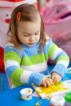 Little girl learning in her nursery at home photo