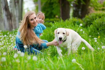 Beautiful woman with little girl and dog outdoors photo