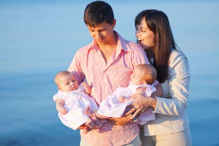 Happy young family with infant twins over sea