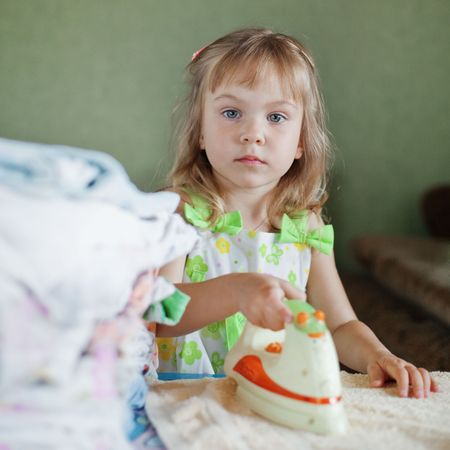 assiduous: Little girl ironing in her nursery at home Stock Photo