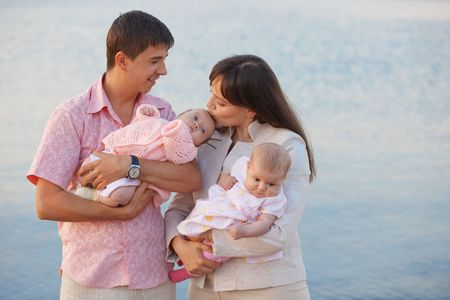 Happy young family with infant kids over sea photo