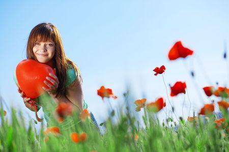 Happy teenage girl holding heart in poppies field