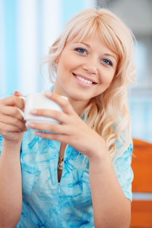Bright portrait of beautiful smiling girl with cup of tea in cafe Stock Photo - 5067204