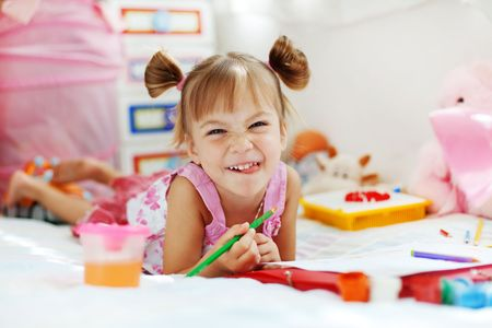 tongue: Little girl painting in her nursery at home
