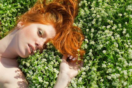 Young beautiful girl lying in fresh grass photo