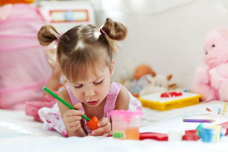 childcare: Little girl painting in her nursery at home