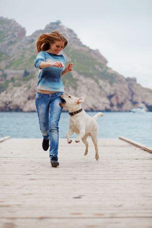 Hermosa niña jugando con su perro en el mar cerca de litera