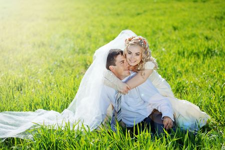 Wedding couple embracing on fresh green grass in sunlight
