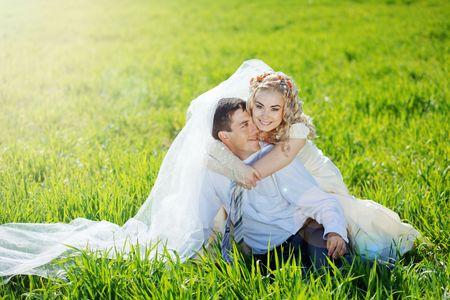 couple enlac�: Wedding couple globale sur l'herbe verte fra�che dans la lumi�re du soleil