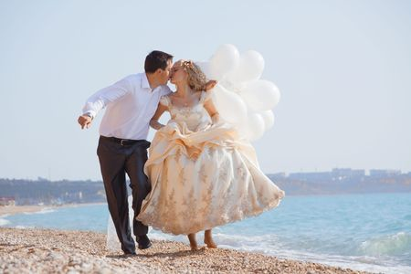 Wedding couple running and kissing on sea coast Stock Photo