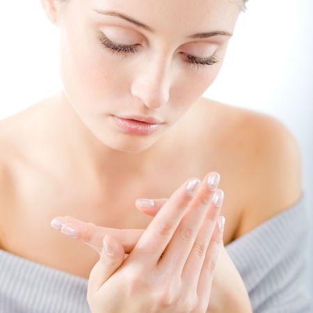 crème: Giovane donna bella applicazione crema mani
