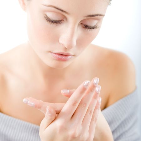 creme: Young beautiful woman applying hands cream Stock Photo