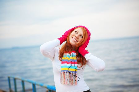 Teenage girl wearing warm clothing listening to music near the sea photo