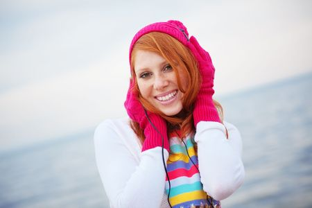 Teenage girl wearing warm clothing listening to music near the sea