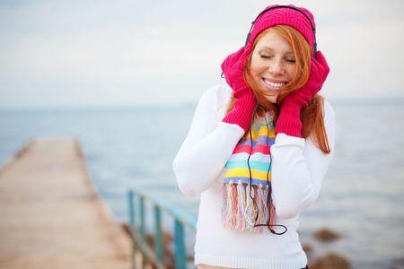 ecoute active: Adolescente portait des v�tements chauds � �couter de la musique pr�s de la mer
