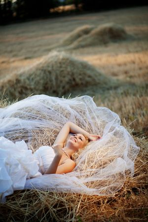 Beautiful bride relaxing in hay stack at her wedding day photo