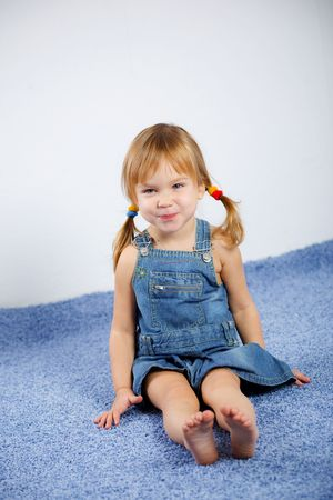 little girl barefoot: Funny playful little girl on blue carpet Stock Photo