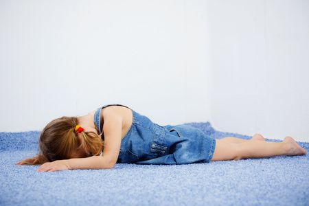 Crying child lying on the floor Stock Photo