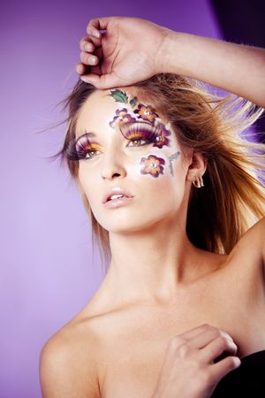 Beautiful fashion model with face-art make-up and blond hair photo