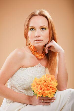 Beautiful bride with orange wedding bouquet photo