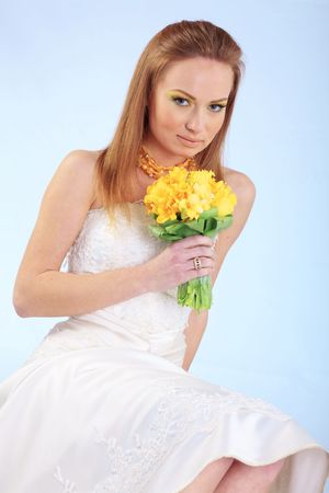 Beautiful bride with bridal colorful makeup posing with wedding bouquet  photo