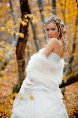 Portrait of beautiful blonde bride in autumn forest photo