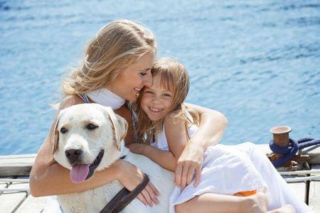 mujer perro: Familia feliz jugando con el perro en el mar, cerca de plaza en el verano de