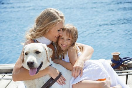 dog summer: Happy family playing with dog on berth near sea in summer