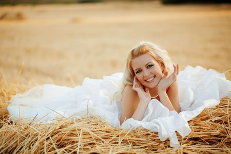 hayloft: Beautiful bride relaxing in hay stack at her wedding day